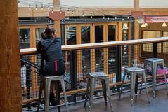 DSC08132 (David Housewright) Tags: pikeplacemarket atrium woman sit stool seattle