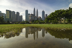 Reflection of the city (mozakim) Tags: kualalumpur klcc petronastwintower reflection water cityscape town city low angle green grass field football soccer day clear sky skyline urban