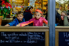 The weather outside is frightful, but... delightful (abtabt) Tags: usa ny newyork nyc manhattan market play girl boy window winter d7001835g children child unitedstatesofamerica food drink littlegirl littleboy glass