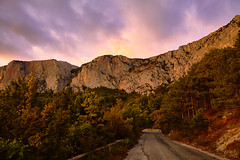 Sunset over the road in the forest in stones mountains (Sergey_pro) Tags: travel environment evening forest morning mountain beautiful sun sunbeam sunlight sunrise sunset background tree journey landscapes leaves marking cloudscape crimea nature outdoor overcast panoramic pinetree road rock dramatic stone sharp sky spring summer asphalt blue clouds grass highway hillock horizon turn view voyage way weather atmosphere cliff pink purple yellow green
