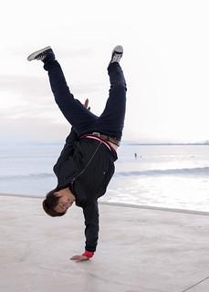 High school boy doing one handed handstanding on beach