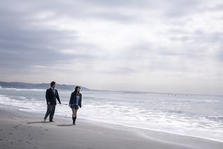 High school student couple walking on beach