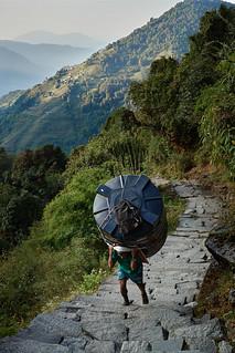 Nepali porter carrying container, Annapurna massif, Nepal