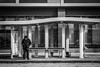 Bus Stop (tim.perdue) Tags: columbus ohio downtown urban city building architecture olympus omd em10mkii tamron 14150mm bus stop street candid man person figure waiting winter cold shelfter design steel glass reflection black white bw monochrome curb sidewalk bench window lines curve