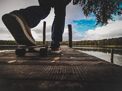 The guy on a skateboard stands on the bridge to jump (ivan_volchek) Tags: people water outdoors lake travel traveling visiting daylight reflection leisure river landscape sky wood pool tree guy man skateboard pier longboard