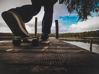 The guy on a skateboard stands on the bridge to jump