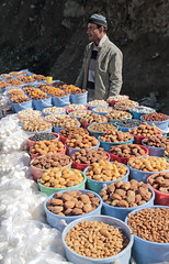 Roadside Offerings (peterkelly) Tags: tajikistan fannmountains roadside digital asia canon 6d gadventures centralasiaadventurealmatytotashkent vendor seller produce driedfruit fruit hat man table apricots almonds nuts bowls buckets yogurtballs yoghurt