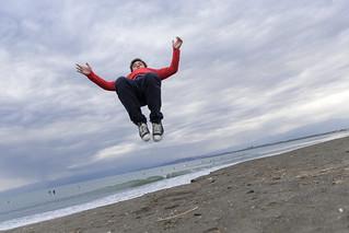 High school boy backflipping on beach