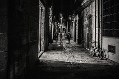 Night in the city..... (Dafydd Penguin) Tags: night city shadows bike people street candid urban back streets alley alleyway barri gotic barcelona catalunya catalonia blackwhite blackandwhite black white monochrome mono noir after dark shots nighthawks nikon df nikkor 35mm af f2d