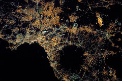 Naples at Night by NASA's Marshall Space Flight Center - Crew aboard the International Space Station took this photograph of the city lights of Naples and the Campania region of southern Italy. The Naples region is one of the brightest in the country; roughly three million people live in and around this metropolitan area.  The different colors of lights in the scene reflect some of the history of development in the area. The green lights are mercury vapor bulbs, an older variety that has been replaced in newer developments by orange sodium bulbs (yellow-orange). To the northeast, the lightless gaps between the homes and businesses are agricultural fields. The bright yellow-orange complex amidst the fields is the CIS emporium, the largest commercial retail facility in Europe. The large black circular area in the photo is Mount Vesuvius, the only active volcano on Europe's mainland.  Image credit: NASA  Read more.  To follow NASA astronauts on twitter, click here.  NASA Media Usage Guidelines