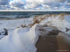 Wind Swept Beach (JamesEyeViewPhotography) Tags: lake michigan beach grass greatlakes sand snow winter water waves wind sky clouds rocks northernmichigan nature landscape lakemichigan jameseyeviewphotography