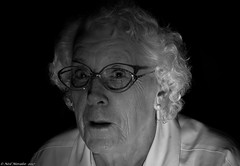 Caught in the flash. (Neil. Moralee) Tags: multiflashneilmoralee neilmoralee woman lady face close candid mature old glasses flash strobe shock black white mono monochrome bw bandw blackandwhite dark blackbackground background low light wrinkles hair flashing nikon d7200 neil moralee motherinlaw mother granny grandmother shadow elderly elder older earring people indoor