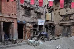 Courtyard waiting earthquake repairs. (posterboy2007) Tags: bhaktapur nepal cobbler courtyard construction shoes stool sand cement sony