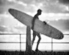 Alien Surf Invasion (Fourteenfoottiger) Tags: odd weird strange surf surfer candid surreal window glass dirty grubby textures silhouette surfboard alien people highcontrast seaside promenade sky clouds fujixt1 abstract mono monochrome blackandwhite street