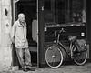 At a little grocery store (andzwe) Tags: dordrecht man doorway bike netherlands dutch nederland blackandwhite zwartwit monochrome panasonicdmcgh4 peinzen verbodenteparkeren groenmarkt melancholiek melancholy fiets sadness