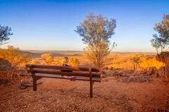 Small Child, Big View (Explored) (*ScottyO*) Tags: brokenhill nsw newsouthwales australia landscape chair bench seat girl child view scene scenic desert red yellow blue sky goldenhour trees leaves outdoor nature vista