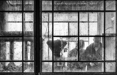 Absorbed (Fourteenfoottiger) Tags: silhouettes men pen shelter grime windows dirty strange mysterious candid street people textures patterns lines backlit light monochrome mono blackandwhite abstract