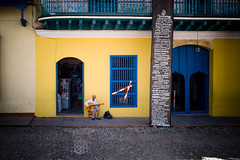 A man playing guitar in front of grocery store at Trinidad Cuba (Sniper1999) Tags: guitar man musican yellow store grocery trinidad cuba m9 leica asph 28mm summicron cron