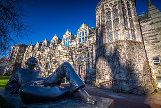 the bronze Reclining Student lounges in the shade against winter sun soaked New Kings building, University of Aberdeen, Aberdeen, Scotland