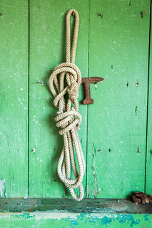 Rope hangs on wall of shed with chipping green paint, Cambridge, Maryland.