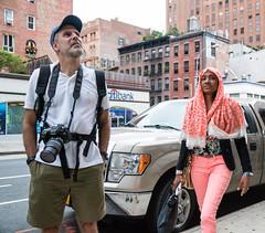 Maybe He's Not a Street Photographer (UrbanphotoZ) Tags: man woman camera canon harness cap beard backpack shawl smartphone salmonpants shorts citibank pickup loftbuildings downtown tribeca manhattan newyorkcity newyork nyc ny