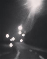 ghosts among us. (helm of deafhorse) Tags: photography blackandwhitephotography blackandwhite monochrome blur blurry unfocused unfocus dark gray black cold road lampposts lights night nighttime nightphotography oldphotos