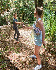 Beating about the Bush 21 (C & R Driver-Burgess) Tags: girl boy preteen young woman niece son curly blonde hair reeds rushes toitoi sticks play fight fencing dual battle pretend fun share shortalls denim track pants lacy singlet black tshirt dry summer sun forest clearing path bush native new zealand aotearoa two together pair cousins