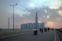 . (Out to Lunch) Tags: dusk evening sky saigon bridge ho chi minh city vietnam motorbikes lightpoles cloud burst blue grey crane urban urbanite suburban apartment buildings development fuji xt1 2814mm