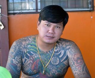 tattooed guy sitting in a food shop