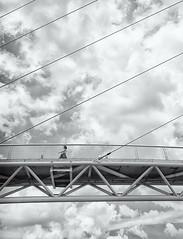 Alone On The Bridge In the Sky (kieronjameslong) Tags: lines cable sky tower pylon bridge cloud wideangle woman person people abstract architecture walk walking monochrome blackandwhite bnw bw leica leicaq street streetphotography urban reallife dailylife minimalism minimalist