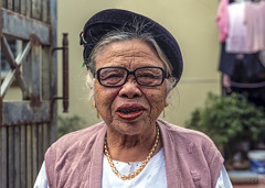 Vietnamese woman (lgflickr1) Tags: vietnam vietnamese hanoi woman old elderly teeth blackteeth outside daytime afternoon cloudy dressedup friendly weathered gold glasses hat wrinkles southeastasia smile rural portrait headshot face travel streetphotography