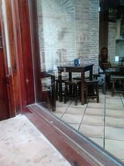 Looking inside Garnacha from the courtyard (d.kevan) Tags: garnacha spain madrid alcaladehenares restaurants tables seats paving serviettes brickwork windows