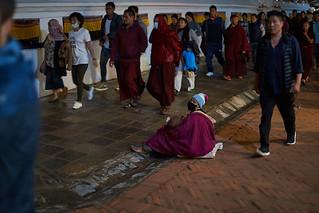 Tibetan beggar in pilgrim flow, Boudhanath, Kathmandu, Nepal