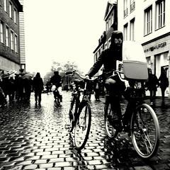 four-wheeled (Bernhardt Franz) Tags: four wheel fourwheeled shortened version gekürzte fassung cyclist fahrradfahrer fahrrad bicycle people cobblestone kopfsteinpflaster blackandwhite bw street buildings facades sky