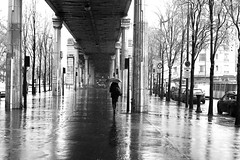 Under the elevated railway (pascalcolin1) Tags: paris13 femme woman neige snow reflets reflection métro subway railway parapluie umbrella pont bridge photoderue streetview urbanarte noiretblanc blackandwhite photopascalcolin canon50mm canon 50mm