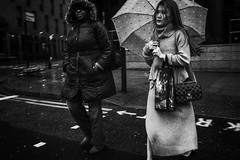 rainy, shitty London (jrockar) Tags: f4 fx 1024 urban city blur motion motionblur noir moody gloomy grey weather rainy rain umbrella woman beautiful pretty girl westfromeast madness ordinary ordinarymadness idiot janrockar jrockar fujix x fujifilm fuji xt2 bnw blackandwhite mono bw candiddecisive moment instant documentary streetphotography streetphoto street london
