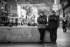 Council benches ain't what they used to be (Silver Machine) Tags: winchester streetphotography street hampshire candid men sitting talking cap concreteblocks antiterrorism shopping outdoor bw blackwhite mono monochrome fujifilm fujifilmxt10 canonfd85mmf18