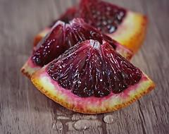 Bloody and juicy (Through Serena's Lens) Tags: pov slice waterdroplets citrus macro tabletop stilllife bokeh dof bloodorange fruit juicy orange 7dwf