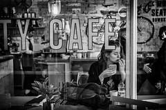 The girl in the window (Daz Smith) Tags: dazsmith fujixt20 fuji xt20 andwhite bath city streetphotography people candid portrait citylife thecity urban streets uk monochrome blancoynegro blackandwhite mono cafe window phone satreflection girl