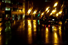 A Rainy Night in St. John's 12 (LongInt57) Tags: city town street road buildings raining rain wet cars vehicles lights reflecting reflections white yellow golden black green woman women person people motion blur walking crossing red stjohns newfoundland canada