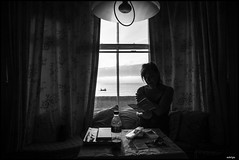 READING IN A DIMLY LIT ROOM (sick4pic) Tags: black white bw blackandwhite contrast dark backlight coke cocacola table woman reading book window sea water ocean coast beach boat sky clouds lamp room hotel bedandbreakfast curtain england silhouette nighty bottle nightdress pillow naturallight ambient natural light