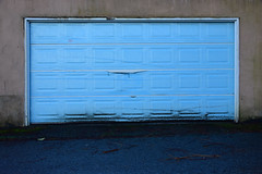 Just leave it on (James_D_Images) Tags: garage door blue plastic film lane alley asphalt brown wall weathered algae dirt moss fallen branches decay