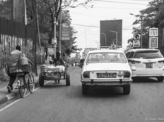 Who is Overtaking Whom - 21st November 2018 (princetontiger) Tags: blackandwhite grayscale monochrome kenya nairobi street streetphotography streetphotograpghy people cart bike bicycle car traffic road