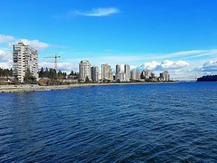 West Vancouver waterfront (walneylad) Tags: westvancouver vancouver ambleside dundarave britishcolumbia canada burrardinlet englishbay pacificocean blue ocean sea water beach rocks sand seawall urban suburban condos buildings sun white clouds waves bluesky march winter nature view scenery waterfront lionsgatebridge