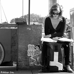 A Summer Day (Akbar Simonse) Tags: amsterdam holland netherlands nederland streetphotography straatfotografie people woman candid reading streetart pasteup vierkant squareformat zwartwit bw blancoynegro bn monochrome akbarsimonse sunglasses shades zonnebril