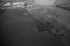 Puddle, Sunset Park Waterfront, Brooklyn (josephkrings) Tags: 1stavenue abandoned brooklyn greenwoodcemetery ilfordhp5 newyork nikkor28105mm13545 nikonn70 sunsetpark blackandwhite puddlereflection warehouse