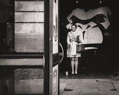 Hideaway (raymorgan4) Tags: hideaway telephone box graffiti wallart monkey picture ape trench coat smoker smoking drinking coffee texting woman stmarystreet cardiff wales cymru cymraeg street shot blackandwhite urban monochrome canon eos m100