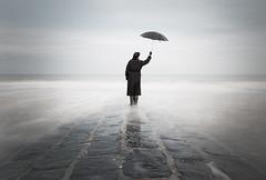 One day I fly away (Schotje) Tags: persoon water zee golfbreker paraplu wolken zwart lange sluitertijd noordzee sky sea people ocean beach