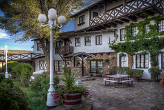 El Rancho Hotel Courtyard (donnieking1811) Tags: newmexico gallup elranchohotel hotel courtyard exterior outdoors lamposts trees flowers bushes table windows wishingwell sky clouds blue ivy hdr canon 60d lightroom photomatixpro
