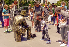 An act of kindness (Marian Pollock) Tags: australia melbourne southbank city victoria statue human child kindness charity crowd people sunny footpath street daytime humanstatue boy